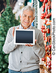 Happy Man Displaying Digital Tablet In Christmas Store -...