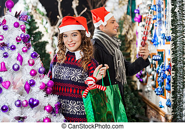 Man And Woman Shopping In Christmas Store - Portrait of...