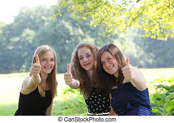 Happy teenage girls giving a thumbs up of approval and...