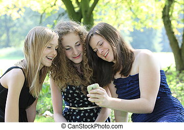 Three happy teenagers reading an sms on a mobile phone as...
