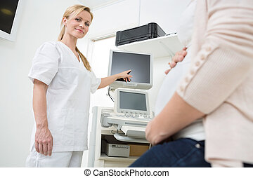 Gynecologist Showing Ultrasound Scan To Pregnant Woman -...