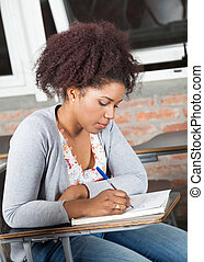 Student Writing Exam At Desk In Classroom