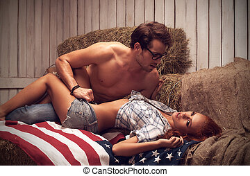 Sexy couple laying on the American flag. Man looking at girl...