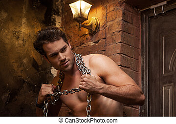 Sexy man with nude torso and chain on neck. Looking away
