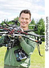 Young Engineer Holding UAV Helicopter - Portrait of happy...
