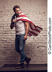 Handsome man walking using American flag like a cloak....