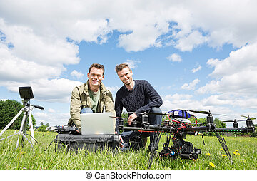 Men Using Laptop Next To UAV - Portrait of men using laptop...