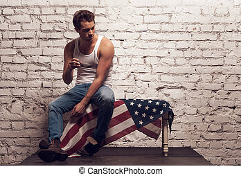 Brutal sexy man sitting on American flag Holding sun glasses...