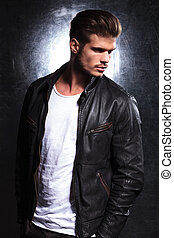 serious young fashion model in leather jacket - side view of...