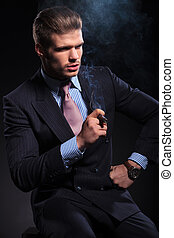 fashion business man smoking a cigar and looking away - side...
