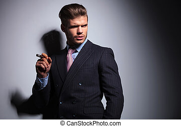 relaxed business man in a classic suit smoking a cigar