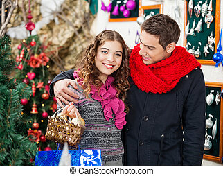 Couple With Bauble Basket In Store - Happy young couple with...