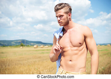 topless man outdoor holding shirt over shoulder - young...