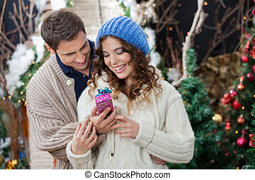 Couple With Christmas Present At Store - Happy young couple...