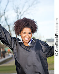 Happy Woman In Graduation Gown On Campus - Portrait of happy...