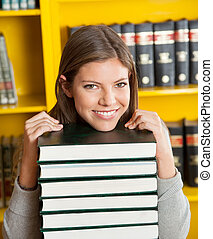 Female Student Resting Chin On Piled Books In Library