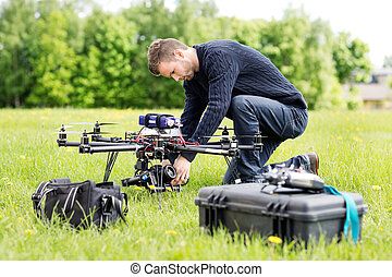 Engineer Setting Camera On UAV Helicopter - Young engineer...