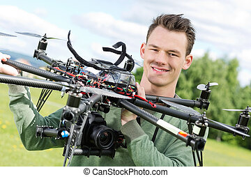 Technician Holding UAV Octocopter - Portrait of confident...