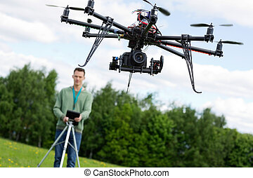 Technician Operating UAV Octocopter - UAV octocopter flying...