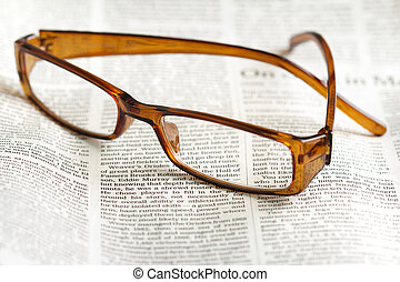 close up of eyeglasses over a daily newspaper