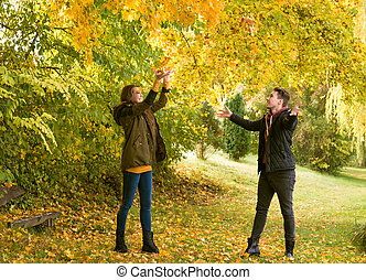 Loving couple toss the leaves, in autumn park