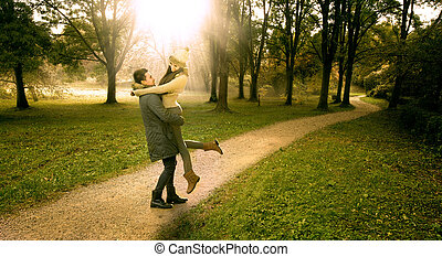 Lover boy lifts the girl in the autumn park