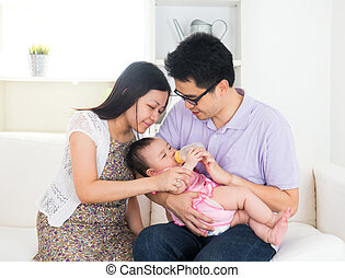 asian parents feeding baby boy at home
