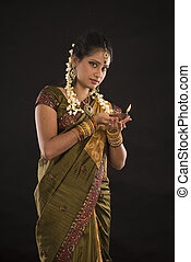 diwali or deepavali photo with female holding oil lamp...