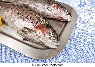 two fresh trout served on a tray