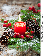 Christmas decoration: fir sprig,candle, cones and berries in...