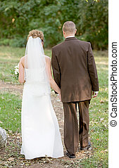 Bride and Groom Walking Along a Path