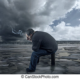 Depressed young man sitting on a chair, smoking a cigarette...