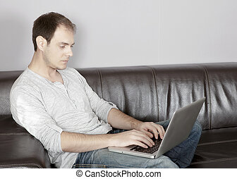 Attractive man typing on his laptop - Attractive middle-aged...