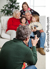 Man Photographing Family Through Smartphone - Rear view of...