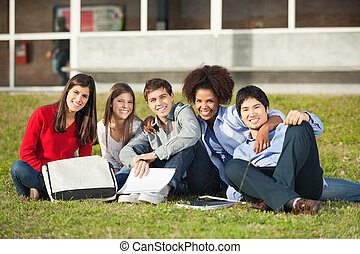 Students Sitting On Grass At College Campus - Portrait of...