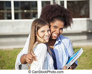 Woman Standing With Arm Around Friend On Campus - Portrait...