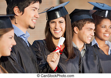 Graduate Student Holding Diploma While Standing With Friends...