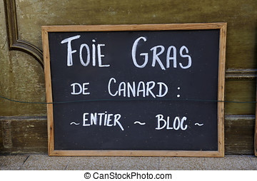 Adboard for foie gras de canard in front of shop in France