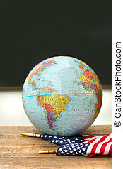 Globe and flag on school desk
