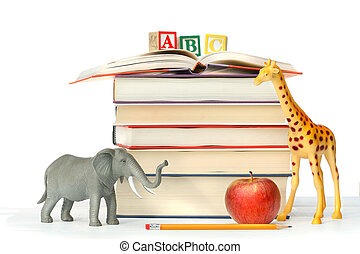 Stack of books with toy animals and apple on white