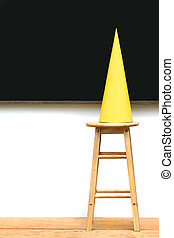 Yellow dunce hat on stool