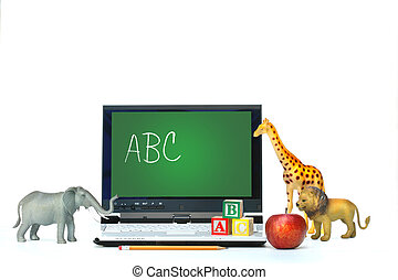 Laptop on desk with toy animals and apple