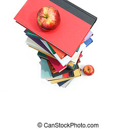 Large piles of books with apples on white