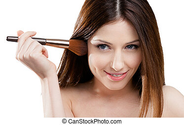 Woman putting on make-up with brush - Woman putting on...
