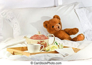 Tea in bed with teddy on white sheets