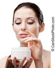 Woman starting to apply face cream - Woman holding cream...