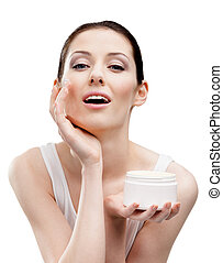 Woman applying cream from container on face, isolated on...