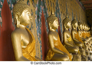 Wat Arun Buddhas - A row of golden Buddhas at the temple of...