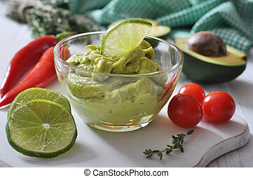 Sauce guacamole in a glass bowl over wooden background