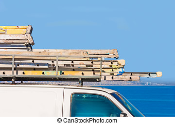 Stack of contractor painting ladders on van roof - Close up...